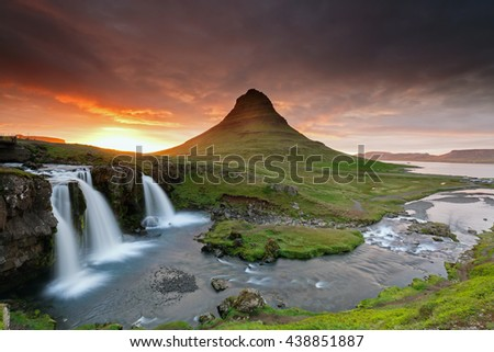 Amazing sunset the top of Kirkjufellsfoss waterfall with Kirkjufell mountain in the background on the north coast of Iceland's Snaefellsnes peninsula taken white a long shutter speed.