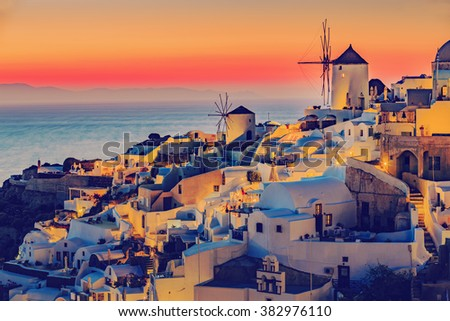 Amazing sunset view with windmills in Oia village on Santorini island in Greece. - stock photo