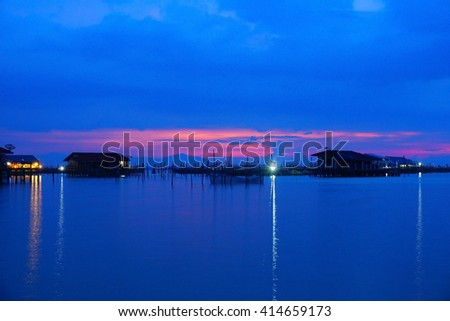 Amazing sunset with silhouette image lake view and fisherman house as a foreground. Soft focus due to long exposure shot. Nature composition:Ideal use for background.