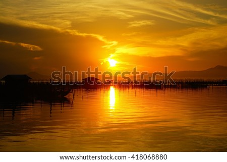 Amazing sunset with silhouette image stone,mountain and Lake view as a foreground. Soft focus due to long exposure shot. Nature composition:Ideal use for background.