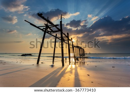 Amazing sunset with sun rays during low tide on Pilai beach in Phang Nga province in Thailand - stock photo