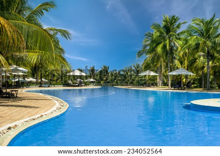 Amazing top view on swimming pool at tropical luxury hotel near ocean - stock photo