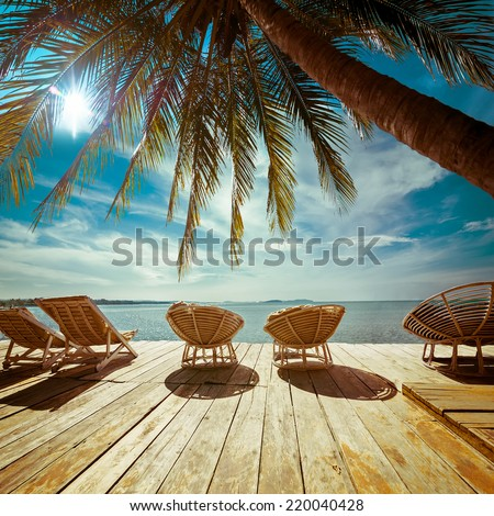 Amazing tropical beach landscape with palm tree and chairs for relaxation on wooden terrace. Travel background in vintage style - stock photo