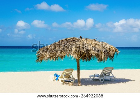 Amazing tropical beach with sunbeds and palm tree umbrellas, golden sand, azure water and blue sky, Caribbean Islands - stock photo