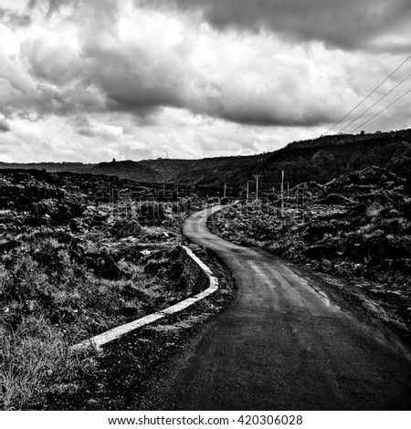 Amazing tropical landscape of rural road across the field volcanic lava. Indonesia - Bali. Black-white photo. - stock photo