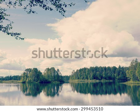 Amazing view by the lake through the branches. Colorful sky with dramatic clouds. Image has a vintage effect applied to create some artistic flavor. - stock photo