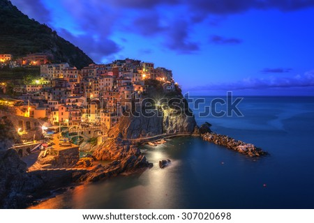 Amazing view of Manarola city at evening light with costal rocks on a foreground. Cinque Terre National Park, Liguria, Italy, Europe. - stock photo