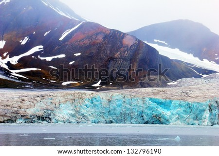 Amazing view of melting blue glacier, calm waters and colorful mountain covered with snow against the background cloudy grey sky with heavy fog in Spitsbergen (Svalbard island), Greenland Sea, Norway - stock photo