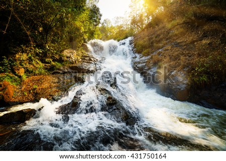 Amazing view of natural waterfall with crystal clear water among green woods in summer. Beautiful sunny forest landscape in Vietnam. The Datanla waterfall is a popular tourist destination of Asia. - stock photo
