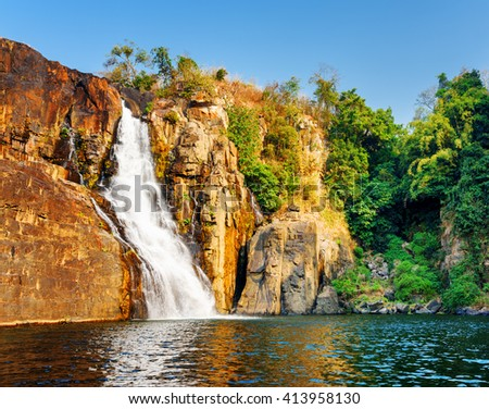 Amazing view of natural waterfall with crystal clear water among rocks and green woods. Beautiful sunny landscape in Vietnam. The Pongour waterfall (PonGour) is a popular tourist destination of Asia. - stock photo