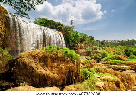Amazing view of waterfall with crystal clear water among green trees on blue sky background in Vietnam. Summer sunny landscape. The Elephant waterfall is a popular tourist destination of Asia. - stock photo