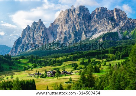 Amazing view on alpine village and beautiful mountains on sunny summer day, The Dolomites Mountains, Italy - stock photo