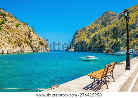 Amazing view on  bench, isthmus and clear sea view in small cosy port of Vathi on Greek Kalymos Island, Greece - stock photo