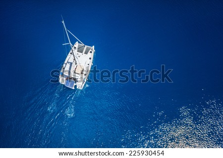 Amazing view to Catamaran cruising in open sea at windy day. Drone view - birds eye angle - stock photo