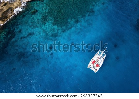 Amazing view to Catamaran cruising in open sea at windy day. Drone view - birds eye angle Coco Island.