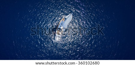 Amazing view to Yacht sailing in open sea at windy day. Drone view - birds eye angle. Yachting theme. Yacht photo. Sailing Yacht. Yacht in sea. Yachting background. - stock photo