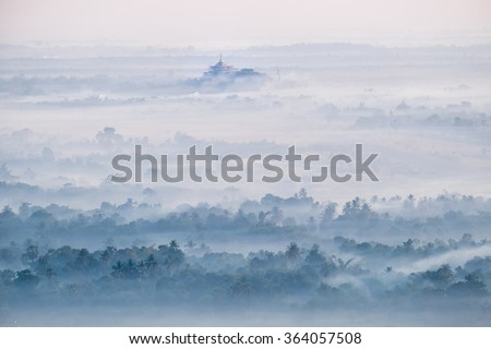 Amazing watercolor view of foggy morning landscape with farm fields and Gabar Lone Pagoda in mist at Thanlwin river. Hpa An, Myanmar (Burma) travel landscapes and destinations - stock photo