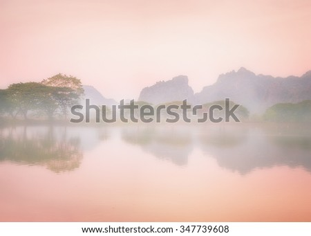 Amazing watercolor view of foggy morning landscape with trees reflection in lake water. Hpa An, Myanmar (Burma) travel landscapes and destinations - stock photo