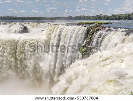 AMAZING WATERFALLS: Waterfall at Iguazu falls with slow shutter speed to blue the water for nature background or waterfall landscape or waterfall background