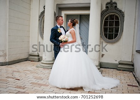 Amazing wedding couple enjoying each other's company by standing next to the columns of a church.
