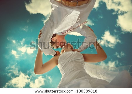 Amazing wedding couple kissing against the backdrop of the beautiful sky. - stock photo