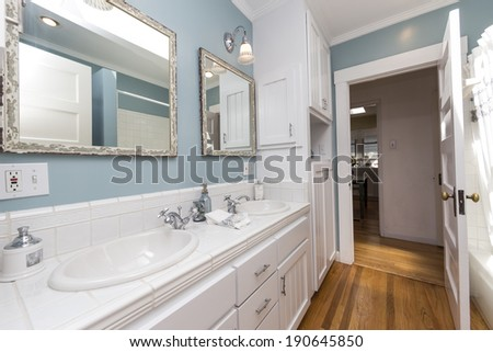 Amazing white remodeled bathroom with fitted counters, wooden floor and nicely decorated shelf.  - stock photo
