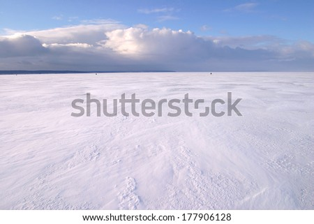 amazing winter landscape beneath the ice of a broad river and beautiful clouds in the blue sky - stock photo