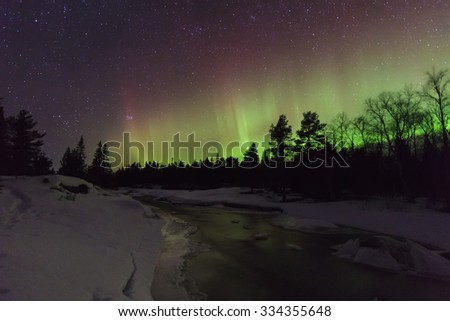 Amazing winter landscape with northern lights and stars. - stock photo