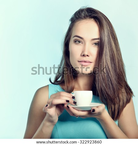 Amazing woman holding cup of coffee. Perfect female beauty. Image toned. - stock photo