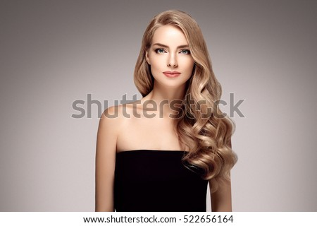 Amazing woman portrait. Beautiful girl with long wavy hair. Blonde model with hairstyle