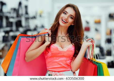 Amazing young girl with long brown hair wearing pink dress standing with colorful shopping bags and smiling, shopping concept, portrait.