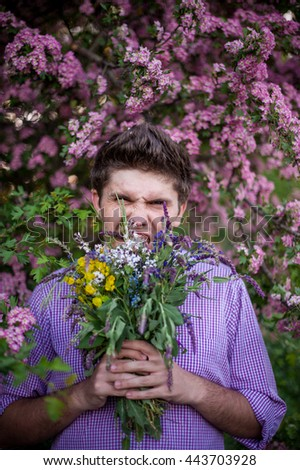 amazing young  man holding a bouquet of colored flowers - stock photo