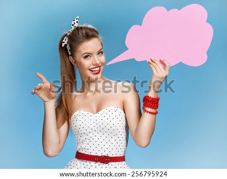 Amazing young woman showing sign speech bubble banner looking happy excited / young American pin-up girl on blue background having idea   - stock photo