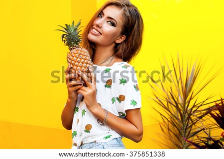 Amazing young woman with fresh fruits posing outdoor,summer concept image, smiling funny,happy summer mood, yellow wall,cool t-shirt with fruit design,summer style outfit women,tan skin,pineapple  - stock photo