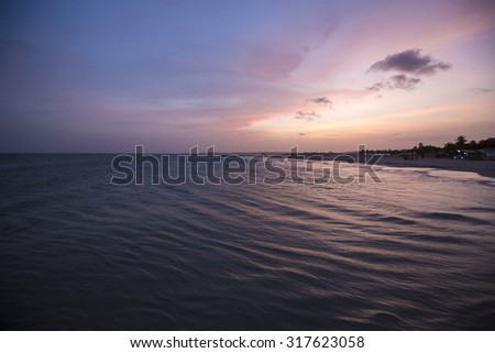 Amazingly colorful sea beach sunset with reflective purple water and bright clouds with distant palm trees. Margarita Island. Venezuela