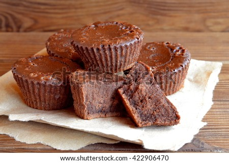 Amazingly delicious chocolate cupcake recipe. Dark chocolate cupcakes. Homemade cakes. Sweet dessert. Close-up. Old wooden background - stock photo