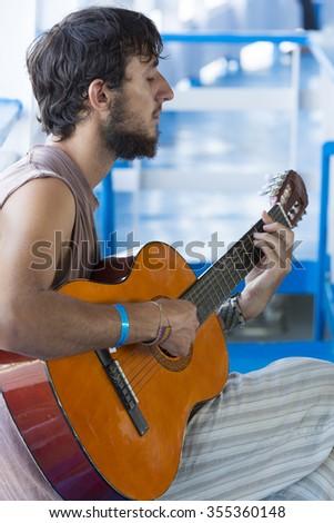 AMAZON, BRAZIL, MARCH 18: Caucasian young man playing guitar on the passenger boat cruising on the Amazon River. Amazonas State, Brazil 2015 - stock photo
