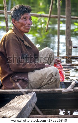 AMAZONIA, PERU - DEC 28: Unidentified Amazonian indigenous man cooking fish over a wooden raft, on December 28, 2009, in Peruvian Amazonia, Loreto, Peru, South America - stock photo
