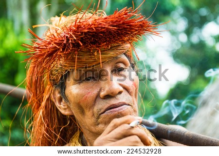 AMAZONIA, PERU - NOV 10, 2010: Unidentified Amazonian indigenous man smokes. Indigenous people of Amazonia are protected by COICA (Coordinator of Indigenous Organizations of the Amazon River Basin) - stock photo