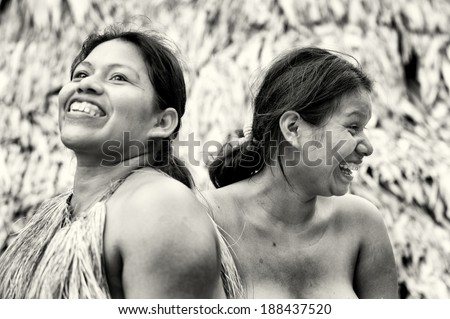 AMAZONIA, PERU - NOV 10, 2010: Unidentified Amazonian indigenous two women laugh. Indigenous people of Amazonia are protected by COICA Coordinator of Indigenous Organizations of the Amazon River Basin - stock photo