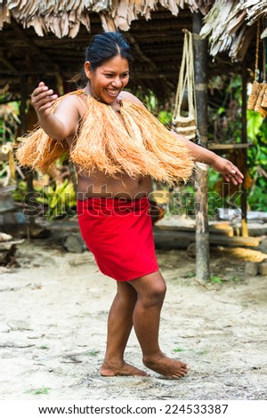 AMAZONIA, PERU - NOV 10, 2010: Unidentified Amazonian indigenous woman dances on the sand. Indigenous people of Amazonia are protected by COICA
