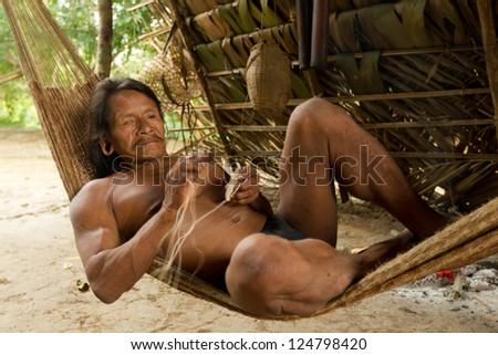 Amazonian indigenous huaorani weaving, focus on face. waorani reserve, Yasuni national park, Ecuador - stock photo