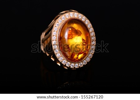 Amber and diamond ring isolated over black - stock photo