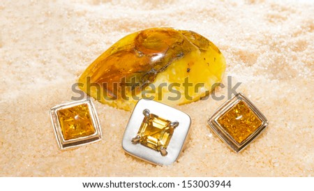 Amber cabochons set in jewellery together with a polished nodule of amber, the fossilized resin of ancient trees that often contains inclusions of seeds and insects - stock photo
