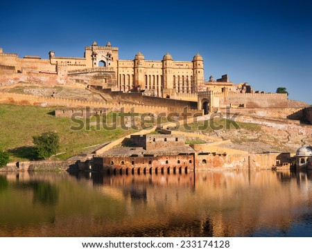 Amber Fort illuminated by warm light of the rising sun and reflected in the lake. Famous Rajasthan landmark located nearby Jaipur city in north-western India. - stock photo