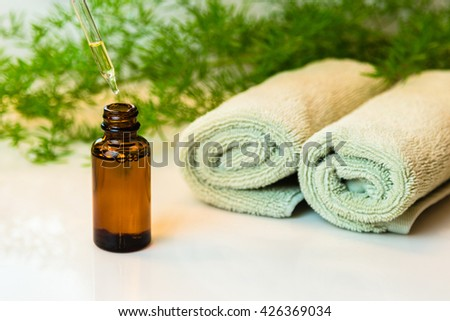 Amber glass bottle with essential oil, with dropper. Rolled green towels in a spa setting. Green plant decor in background. Bathroom white countertop.