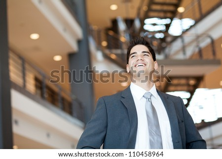 ambitious and optimistic young businessman looking up - stock photo