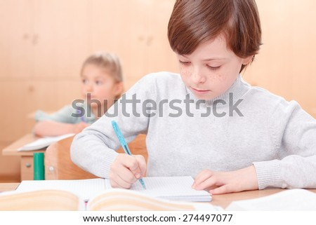 Ambitious boy. Little boy writing something in his copy book during classes.