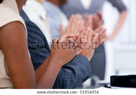 Ambitious business team applauding in a meeting in a company
