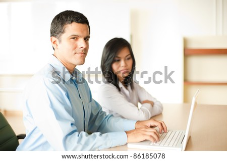Ambitious Hispanic professional man sitting at office conference room desk, smiling, looking at camera, typing at laptop, leading one on one meeting with Asian coworker looking down at screen